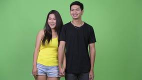 Молодые счастливые азиатские пары думая пока держащ руки совместно сток-видео
