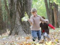 Молодые счастливые дети на естественном backgrou осени Стоковые Фотографии RF