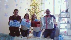 Молодые счастливые друзья празднуя рождество сидят перед рождественской елкой, держат подарочные коробки и дают коробки к акции видеоматериалы