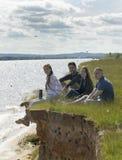Молодые счастливые друзья сидя на холме наслаждаясь воссозданием outdoors Стоковые Фото