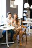 Молодые счастливые европейские пары сидя на кафе и отдыхать стоковая фотография rf
