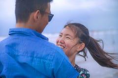 Молодые счастливые и красивые китайские азиатские пары с женщиной обнимают ее парня романтичный и прижимаются на пляже Стоковая Фотография