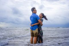 Молодые счастливые и красивые китайские азиатские пары с женщиной обнимают ее парня романтичный и прижимаются на пляже Стоковое Фото