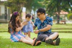 Молодые счастливые и любящие азиатские японские пары родителей наслаждаясь вместе со сладким ребенком дочери сидя на траве на зел стоковые фото