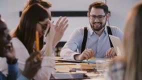 Молодые счастливые корпоративные работники штата беседуя и усмехаясь акции видеоматериалы