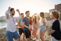 Молодые счастливые люди partying на пляже Стоковое Фото