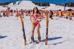 Молодые счастливые милые женщины на горе катаются на лыжах в красочном бикини Стоковое Изображение