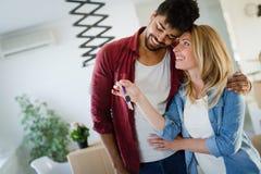 Молодые счастливые пары двигая в новый дом и распаковывая коробки Стоковые Изображения