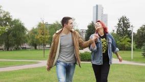 Молодые счастливые пары держа руки и идя в парк города сток-видео