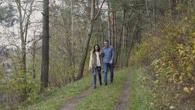 Молодые счастливые пары идя в красивый лес 4K осени акции видеоматериалы