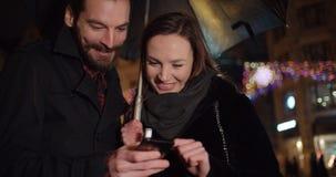 Молодые счастливые пары используя smartphone на ноче Стоковые Изображения