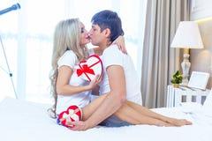 Молодые счастливые пары лежа в кровати, испанский человек дают конверт настоящего момента сюрприза женщины с лентой, торжеством г Стоковое Изображение RF
