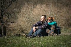Молодые счастливые пары распологая в парк наслаждаясь днем совместно стоковые фотографии rf