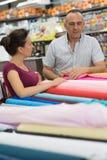 Молодые счастливые пары семьи имея потеху в магазине выбирая ткань Стоковое Изображение