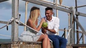 Молодые счастливые пары сидя на смеяться над деревянной пристани говоря и выпивая кокос на предпосылке голубого неба романтично акции видеоматериалы