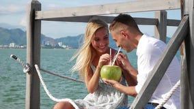 Молодые счастливые пары сидя на смеяться над деревянной пристани говоря и выпивая кокос на голубой предпосылке моря романтично сток-видео