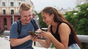 Молодые счастливые пары смотря экран smartphone и смеясь над на улице города видеоматериал