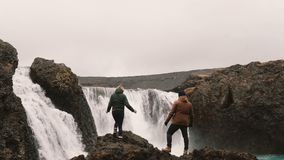 Молодые счастливые пары совместно для того чтобы увидеть мощный водопад в Исландии Повышение человека и женщины вручает вверх акции видеоматериалы