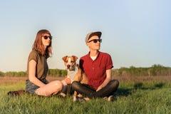 Молодые счастливые пары человека и женщины с терьером d Стаффордшира стоковая фотография