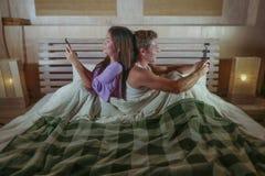 Молодые счастливые привлекательные пары этничности смешивания при азиатская женщина и кавказский человек сидя на кровати спина к  стоковые фото