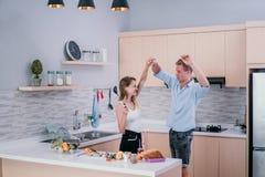 Молодые счастливые руки владением пар и танцы начала когда подготовьте для варить стоковое фото rf