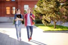 Молодые счастливые студенты с книгами и примечания в университетском кампусе Стоковое Фото