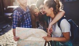 Молодые счастливые туристы sightseeing в городе стоковые изображения