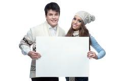 Молодые ся пары зимы держа большой знак Стоковое Изображение