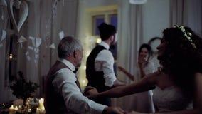 Молодые танцы невесты с дедом и другими гостями на приеме по случаю бракосочетания сток-видео