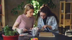 Молодые творческие дизайнеры смотрят фото внимательно и обсуждают их пока сидящ совместно на таблице Съемка лотка видеоматериал
