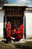 молодые тибетские буддийские монахи ждать вне их школы под towering горами стоковая фотография