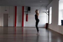 Молодые тонкие белокурые скачки с веревочкой в спортзале Девушка делая cardio тренировки в студии фитнеса стоковые фото