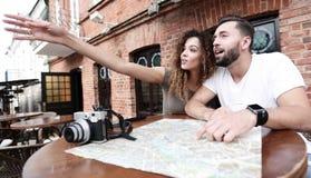 Молодые туристы выпивая кофе на кафе и читая карту города Стоковое Изображение