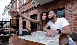 Молодые туристы выпивая кофе на кафе и читая карту города Стоковое фото RF