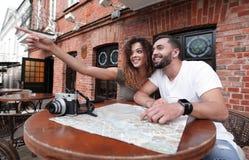 Молодые туристы выпивая кофе на кафе и читая карту города Стоковое Фото
