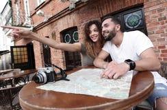 Молодые туристы выпивая кофе на кафе и читая карту города Стоковые Изображения
