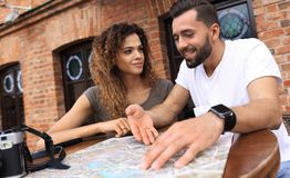 Молодые туристы выпивая кофе на кафе и читая карту города Стоковые Фото