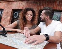Молодые туристы выпивая кофе на кафе и читая карту города Стоковые Фотографии RF