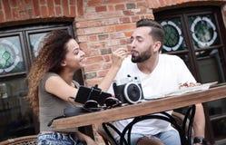 Молодые туристы есть завтрак на таблице ресторана вне стороны Стоковая Фотография