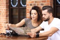 Молодые туристы имея кофе на кафе и читая карту Стоковые Изображения RF