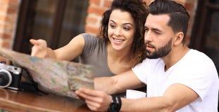 Молодые туристы имея кофе на кафе и читая карту Стоковые Фото