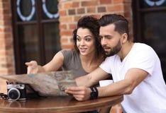 Молодые туристы имея кофе на кафе и читая карту Стоковые Изображения