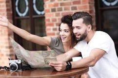 Молодые туристы имея кофе на кафе и читая карту Стоковая Фотография