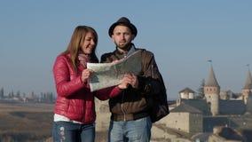 Молодые туристы просматривая местную карту на предпосылке старинной улицы, ища новое назначение outdoors сток-видео