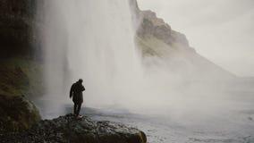 Молодые туристы с камерой действия около водопада Gljufrabui в Исландии Укомплектуйте личным составом смотреть на известном визир видеоматериал
