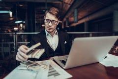 Молодые удерживание бизнесмена и деньги повторных подсчетов стоковое изображение