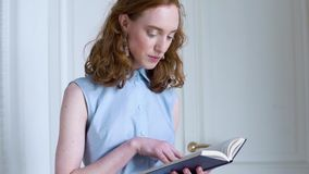 Молодые удерживание и чтение девушки redhead книга в белой комнате сток-видео