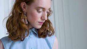 Молодые удерживание и чтение девушки redhead книга в белой комнате видеоматериал