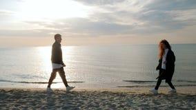 Молодые ультрамодные человек и женщина, люди на песке приставают к берегу, счастливые пожененные взрослые пары имея потеху, играт видеоматериал