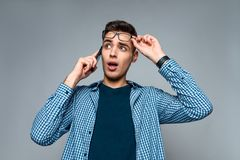 Молодые умные беседы парня по телефону, регулируя стекла стоковые изображения